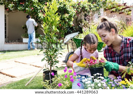 Mother and daughter gardening together in garden on a sunny day - stock photo