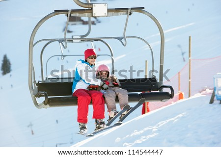 Mother And Daughter Getting Off chair Lift On Ski Holiday In Mountains - stock photo