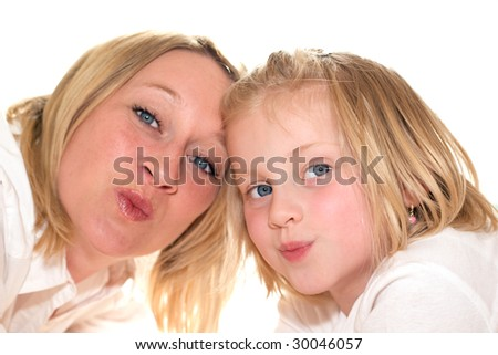 Mother and daughter giving kiss to camera - stock photo