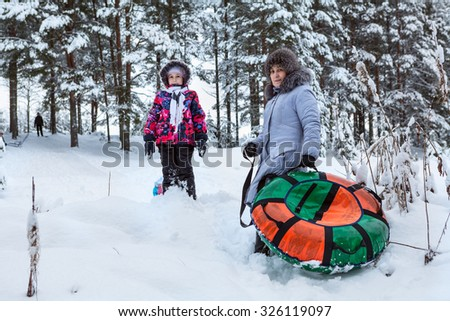 Mother and daughter going for a walk, riding on an inflatable tube from slides - stock photo