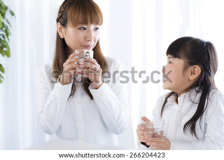 mother and daughter have a drink of water - stock photo