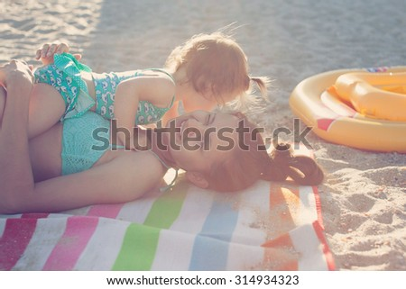 Mother and daughter have fun on the beach - stock photo