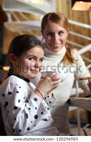 Mother and daughter having a snack - stock photo