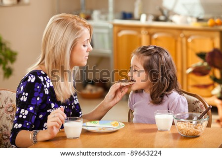 mother and daughter having breakfast: eating chocolate cream on a slice of bread - stock photo