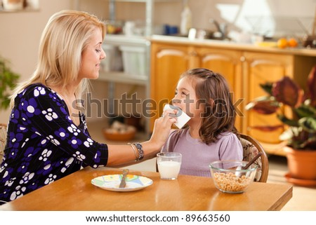 mother and daughter having breakfast: milk and cereals - stock photo