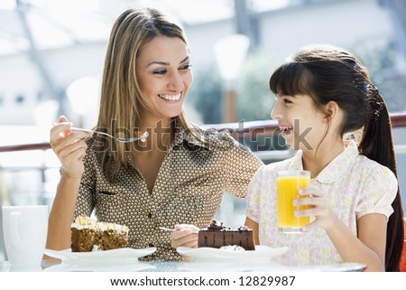 Mother and daughter having cake and juice at cafe - stock photo