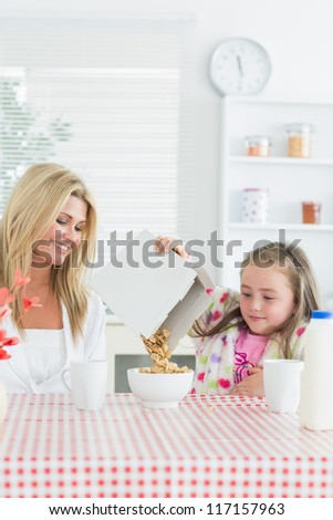 Mother and daughter having cereal at breakfast - stock photo