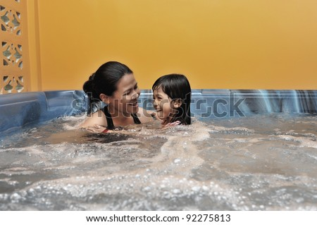 Mother and daughter having fun during Jacuzzi session. - stock photo