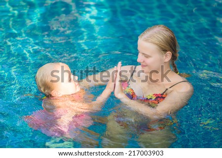 Mother and daughter having fun in pool at tropical beach resort - stock photo