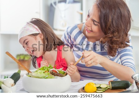 Mother and daughter having fun in the kitchen making vegetable  salad  - stock photo