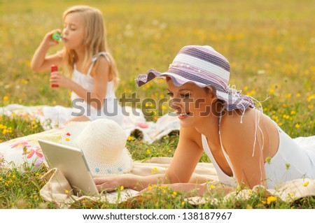 Mother and daughter having fun in the nature on sunny summer day. - stock photo