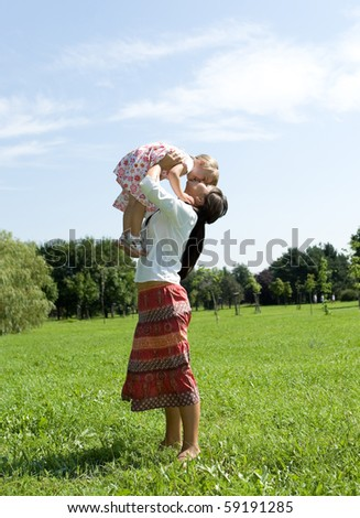 mother and daughter having fun on meadow - stock photo