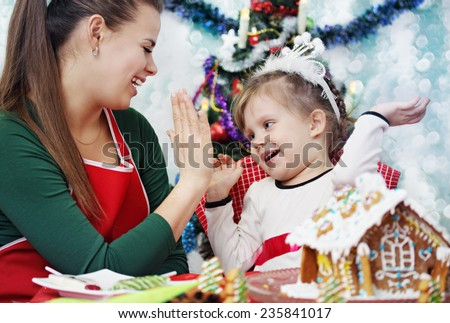 Mother and daughter having fun playing, clapping her hands - stock photo