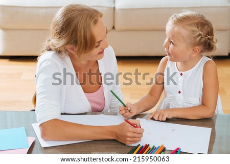 Mother and daughter having fun while drawing at home - stock photo
