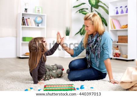 Mother and daughter having fun while sitting on the carpet in the living room - stock photo