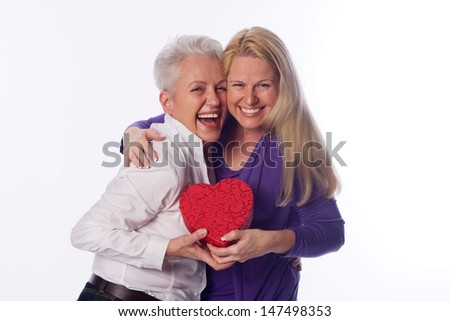 Mother and daughter holding a present in there hands - stock photo