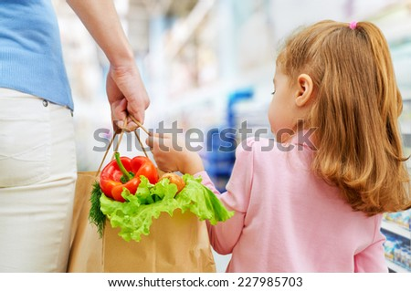 mother and daughter holding fruit - stock photo
