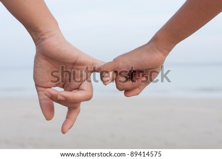 Mother and daughter holding hand together on the beach - stock photo