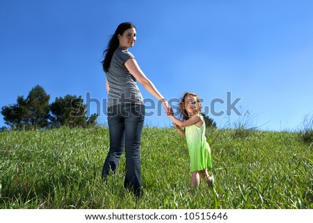 Mother and daughter holding hands in a field - stock photo