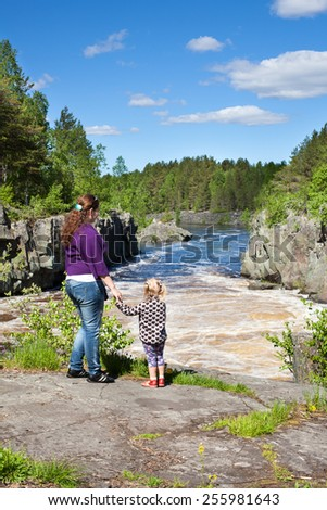 Mother and daughter holding hands standing near a waterfall at summer - stock photo