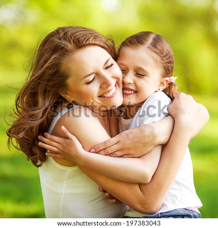 mother and daughter hugging in love playing in the park - stock photo