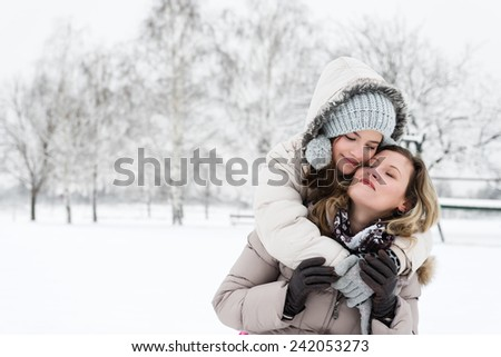 Mother and daughter hugging outdoors in the wintry landscape.Copy space - stock photo