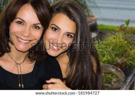 Mother and daughter in a affectionate pose outdoors. - stock photo