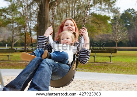 Mother and daughter in a swing having fun at the park playground - stock photo