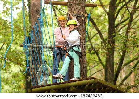 mother and daughter in climbing equipment to overcome obstacles between high trees - stock photo