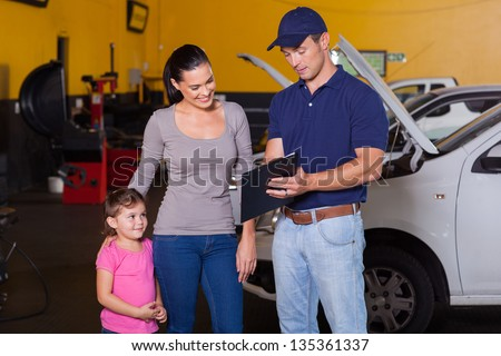 mother and daughter in garage with auto mechanic - stock photo