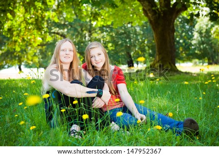 Mother and daughter in green summer nature. Shallow DOF, girl's face in focus. - stock photo