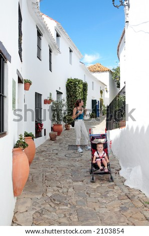 Mother and Daughter in narrow cobbled streets of white Pueblo on vacation in Spain - stock photo