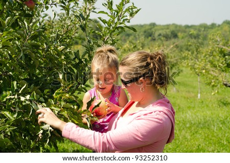 mother and daughter in orchard - stock photo