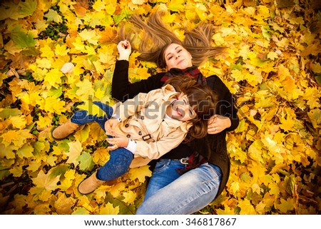 Mother and daughter in park Mother and daughter playing in park. They are lying on dry autumn leaves in the park,resting - stock photo