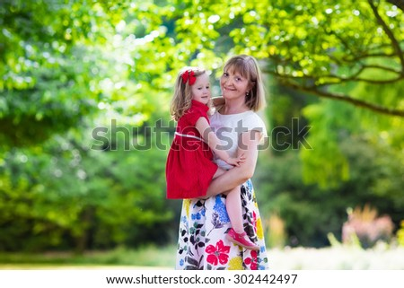 Mother and daughter in party dress enjoying summer sunny day in a park. Grandmother playing with little toddler girl in a forest. Summer outdoor fun in the garden. Grandparents and kids on a meadow. - stock photo