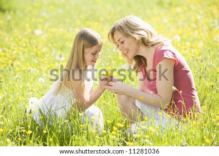 Mother and daughter in summer field - stock photo
