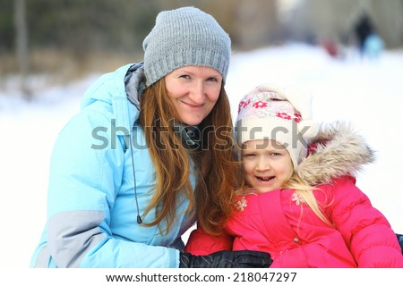 mother and daughter in winter outdoors  - stock photo