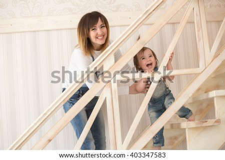 Mother and daughter indoors sitting on the stairs - stock photo