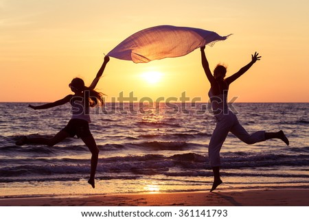 Mother and daughter jumping on the beach at the sunset time. Concept of happy friendly family. - stock photo