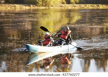 Mother and daughter kayaking together on a lake, close up - stock photo