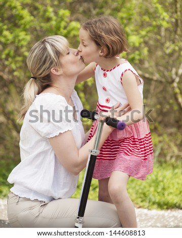 Mother and daughter kissing in park with scooter - stock photo