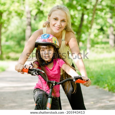 mother and daughter learning to ride a bicycle - stock photo