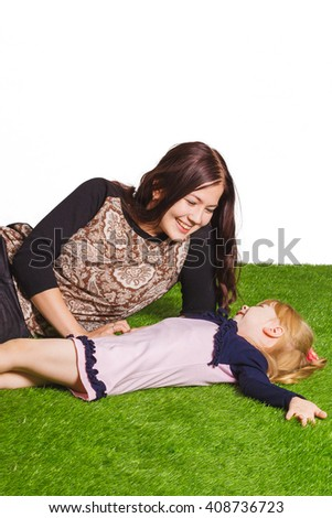 mother and daughter lie on the grass isolated on white background - stock photo