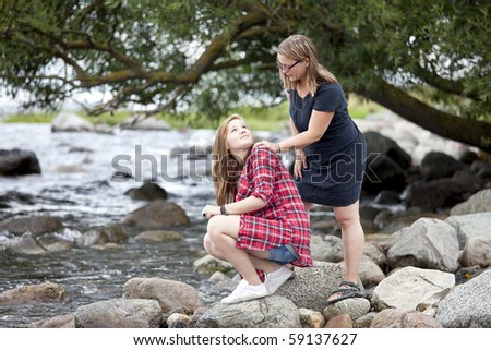 Mother and daughter looking at each other. Standing outside. - stock photo