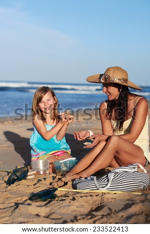Mother and daughter looking at shell collection together interacting at the beach on weekend leisure fun - stock photo