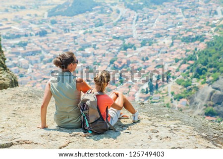 Mother and daughter looking at the town of Kalambaka bird's eye view. Meteora, Greece. - stock photo