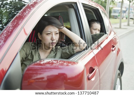 Mother and Daughter Looking Frustrated Out the Window of a Car - stock photo