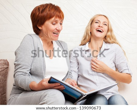 Mother and daughter looking photo book. Two laughing smiling women at home - stock photo