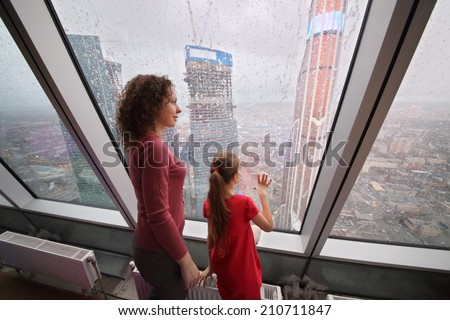 Mother and daughter looking through a large window on the modern city - stock photo
