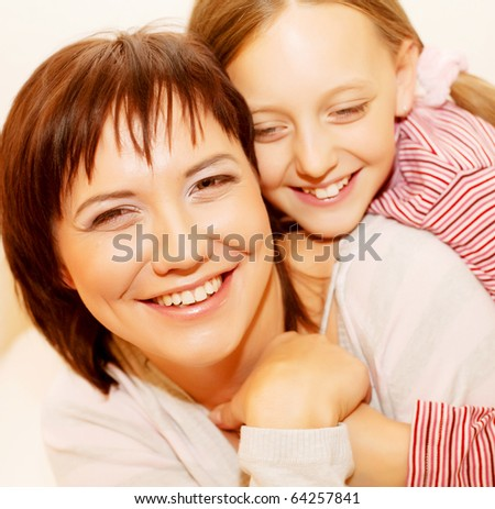 Mother and daughter looking to camera - stock photo